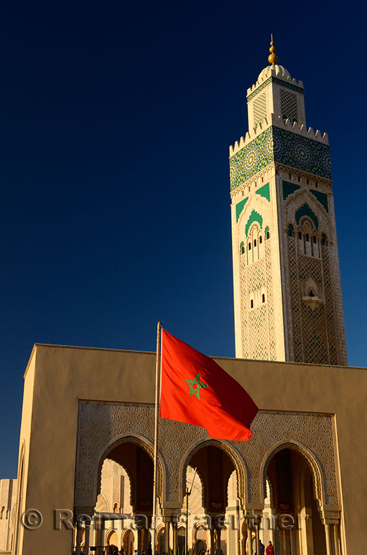 Moroccan flag at the Hassan II Mosque in Casablanca with blue sky