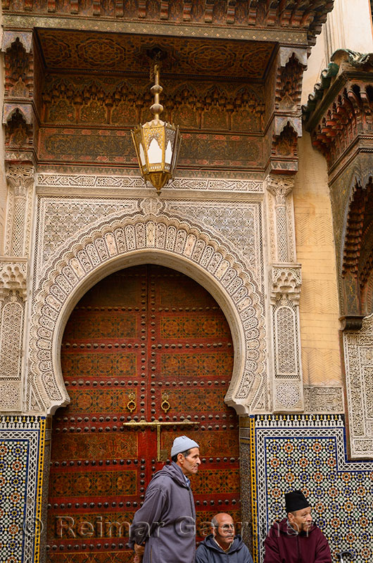 Men waiting at the ornate door of Sidi Ahmed Tijani Mosque with intricate stone carving in Fes Morocco