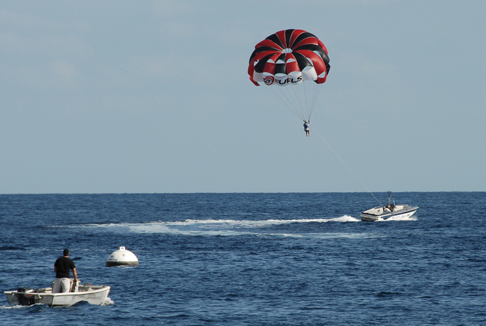 Some parasailing activity offshore.