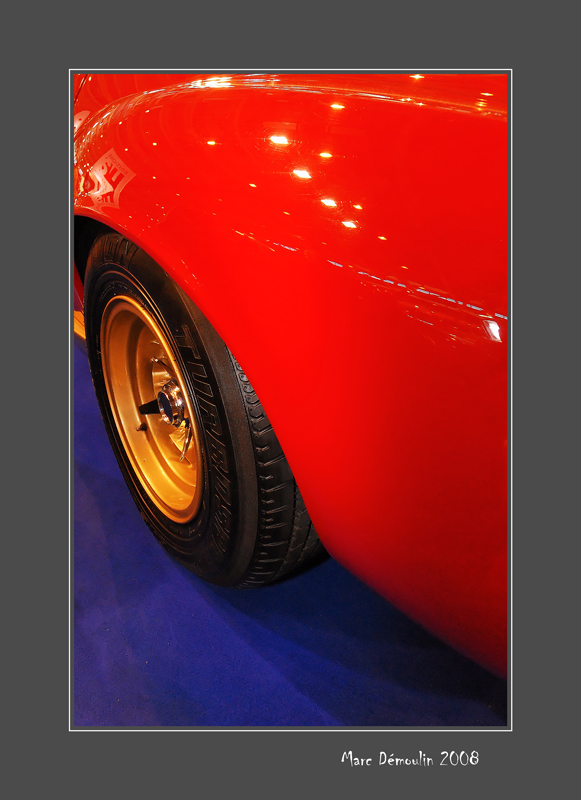 Golden rim of a red Lamborghini on a blue carpet