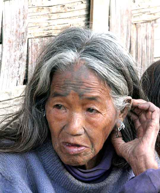 Chang Naga lady in Tuensang Village with tattoos that shall ward off tigers.
