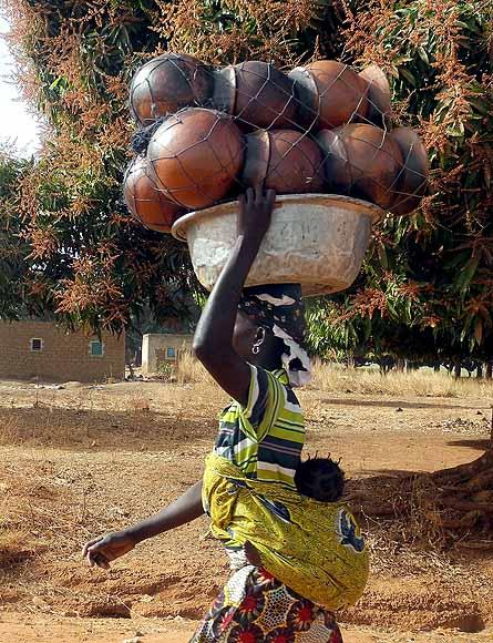 Heavy clay pots and the baby are carried many kilometres to the next market, Burkina Faso