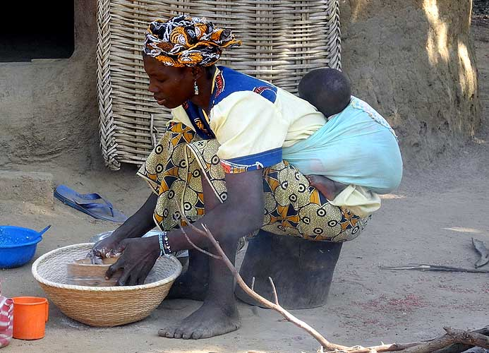 Mother doing housework while carrying her baby, Burkina Faso