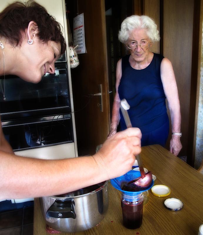 Simone checks that Marie-Luce fills properly the jars...