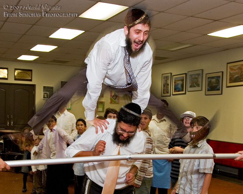 Menasha, brother of the Bar Mitzvah, leaping over older brother and the Limbo Bar