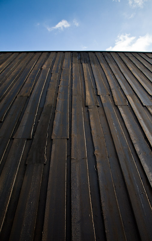 The tarred wooden walls of the new art museum Artipelag