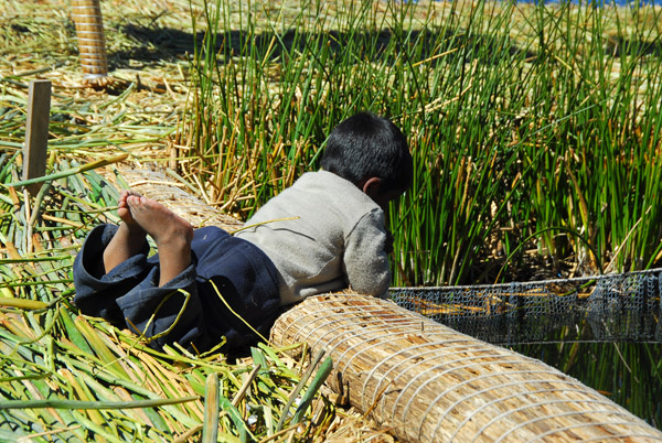 Uros boy playing alongside the fish pen