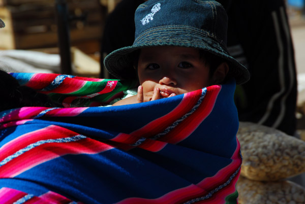 Child carried on the back wrapped in a blanket