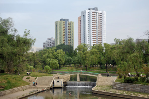River with a small waterfall and pedestrian bridge, Pyongyang