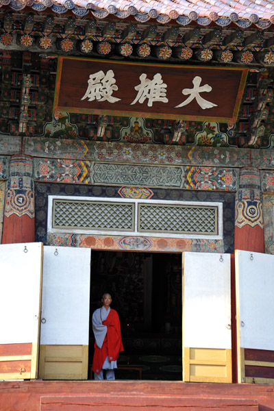 Monk waiting at the door of the Taeung Hall