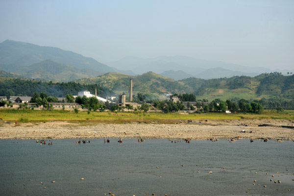 Factory town with North Koreans enjoying the Chongchon River on a hot day