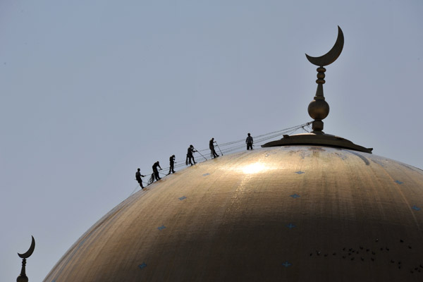 Workers on the roof polishing the dome of the Kipchak Grand Mosque