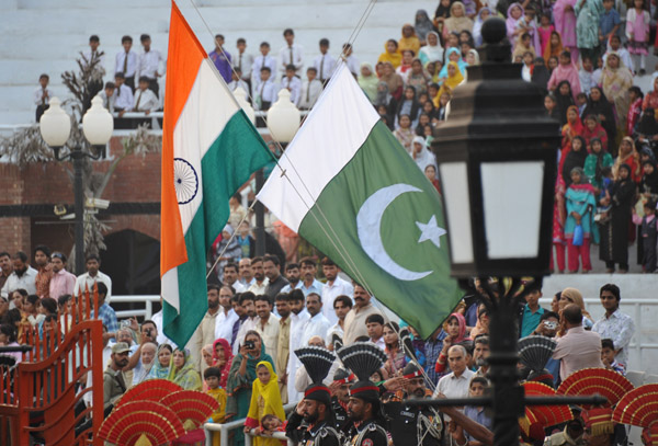 The flags of India and Pakistan cross as they are lowered at the end of the day