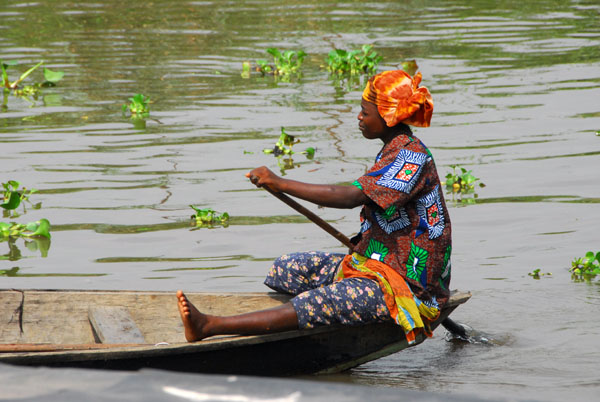 Woman paddling her canoe through the streets of Ganvié