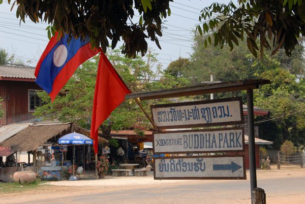 Lao national and party flags at the entrace to Buddha Park