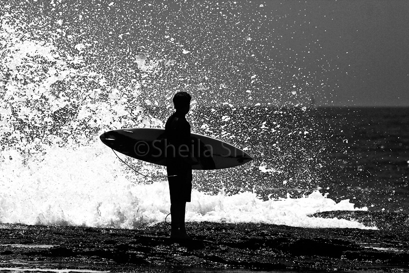 Surfer waiting with board in monochrome
