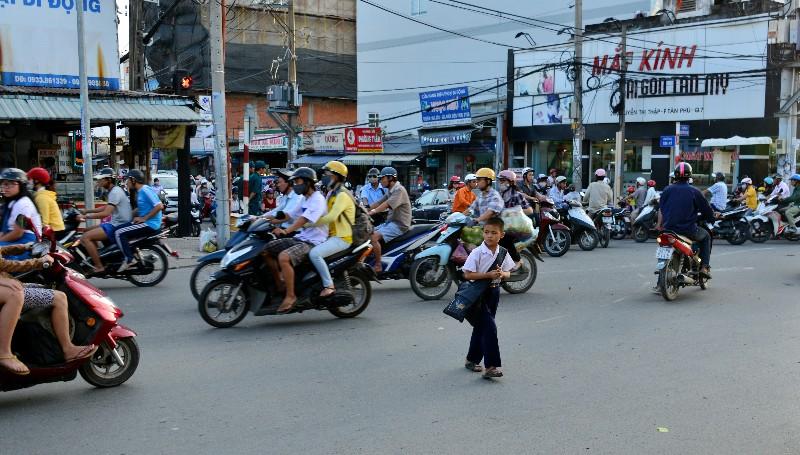 brave kid, rush hour, crazy scooter traffics, Saigon, Vietnam