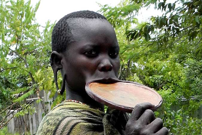 Surma woman with an extremely big lip plate and stretched ear lobes for plates; south-western Ethiopia.