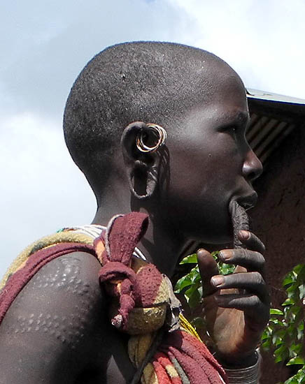 Surma woman with scarification marks and streched lower lip and ear lobes for plates;  south-western Ethiopia.