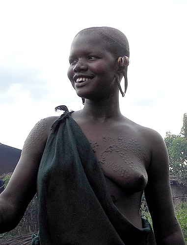 Surma girl with scarification marks and streched ear lobes for plates;  south-western Ethiopia.