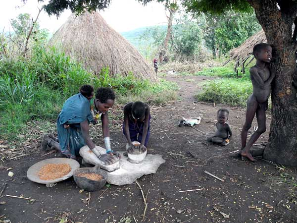 Surma woman and her daughter grinding maize;  south-western Ethiopia.
