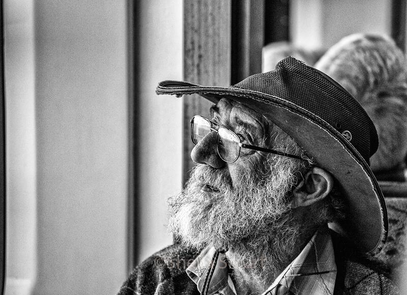 Man in hat on ferry in mono