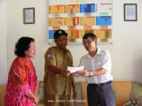 Handing the money order to the school principal, Mr. Suranto