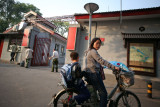 Mother taking son home from school on a bicycle