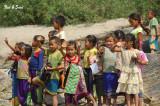 children waving at passing boats