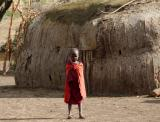 Masai child in front of hut