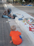 Simon watches a local artist paint our curb