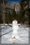 A snowman is embracing the sunny day with Yosemite Falls in the background