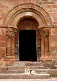 Dog at the romanesque door - Pineda
