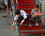 Tibetan boys play with their watermelon car and boat.