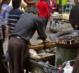 Roasting horse chestnuts outside market. Jishou City, Hunan Province, China