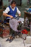 Shoerepairman resoling shoe. Jishou City, Hunan Province, China
