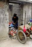 Hmong (Miao) elder picking through garbage for recyclables.