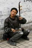 He is blind, loves to play this intrument and sing and does not ask for money.