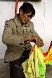 Sewing on the dragon tail for new years. Pan Zhai Village, Guizhou, China