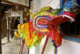 Sewing on the dragon tail for the New Year celebration. Pan Zhai Village, Guizhou, China