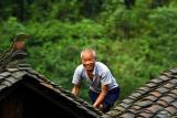 Hmong elder working on his roof.