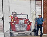 The Valley Mills Chief of Police standing beside a fire truck mural.