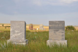 Two tombstones and two grain elevators.