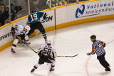 Sidney Crosby and Joe Thornton fight for the puck