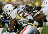 Yellow Jackets OLB Anthony Egbuniwe ties up Hurricanes RB Damien Berry at the line of scrimmage