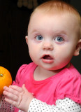 Grace trying to eat an orange