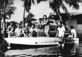1947 - Jerry Oliver (front of boat, arm on edge) and Allapattah neighbors after the Flood of 1947 caused by a hurricane