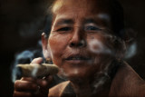 Market vendor enjoying her cheroot.