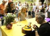 Tommy Emmanuel signs a mini-guitar for a fan