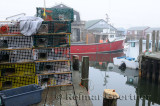 Wire lobster traps on dock and boats in fog at Fishermans Cove Eastern Passage Halifax Nova Scotia